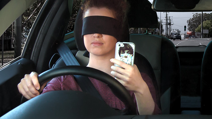 Woman blindfolded in car on phone