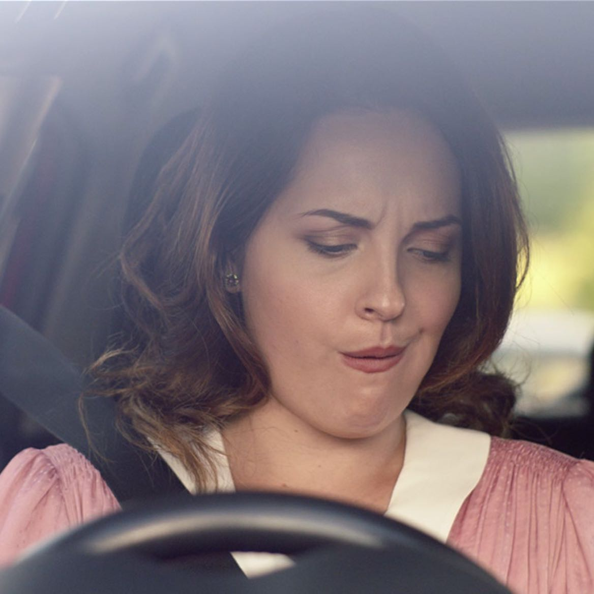 Close up shot of woman sitting in car and pulling a funny face looking down at the centre console