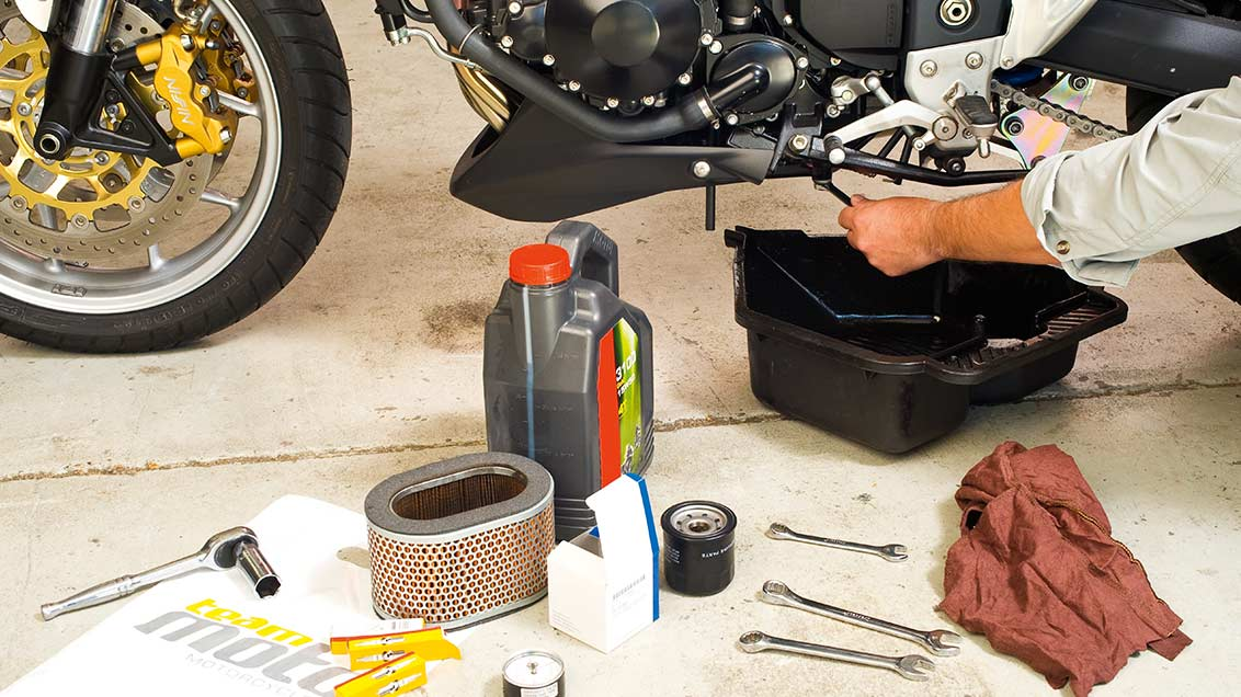 Lower view of motorcycle having an oil change with various tools laying on the floor near it