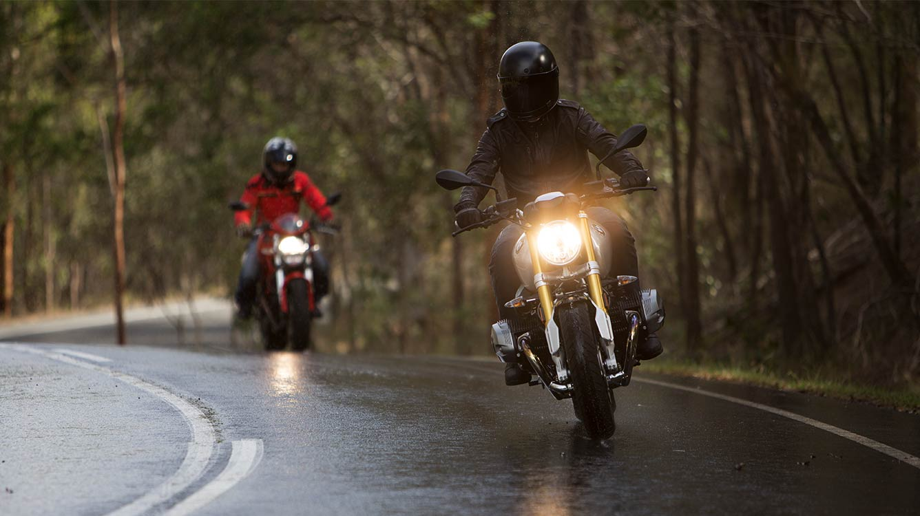 View of two motorcyle riders moving towards camera on a wet road surface