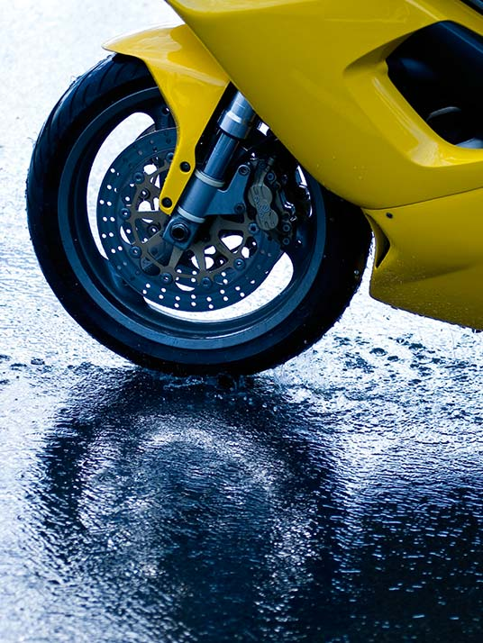 View of front tyre of yellow sports bike on a wet road surface