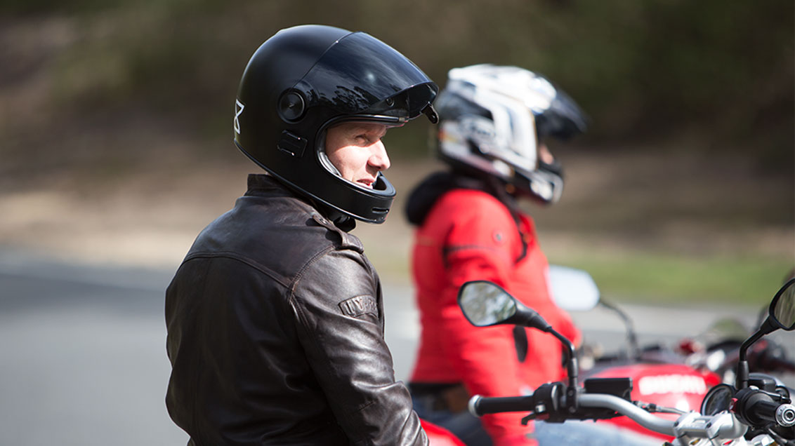 View of male motorcycle rider with open face helmet parked and staring off into the distance