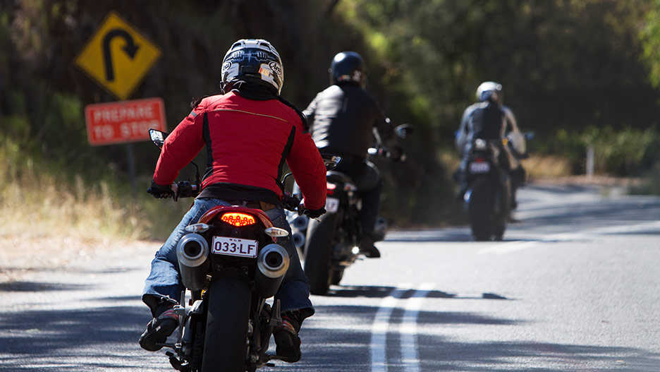 Rear view of three motorcycle riders on group ride