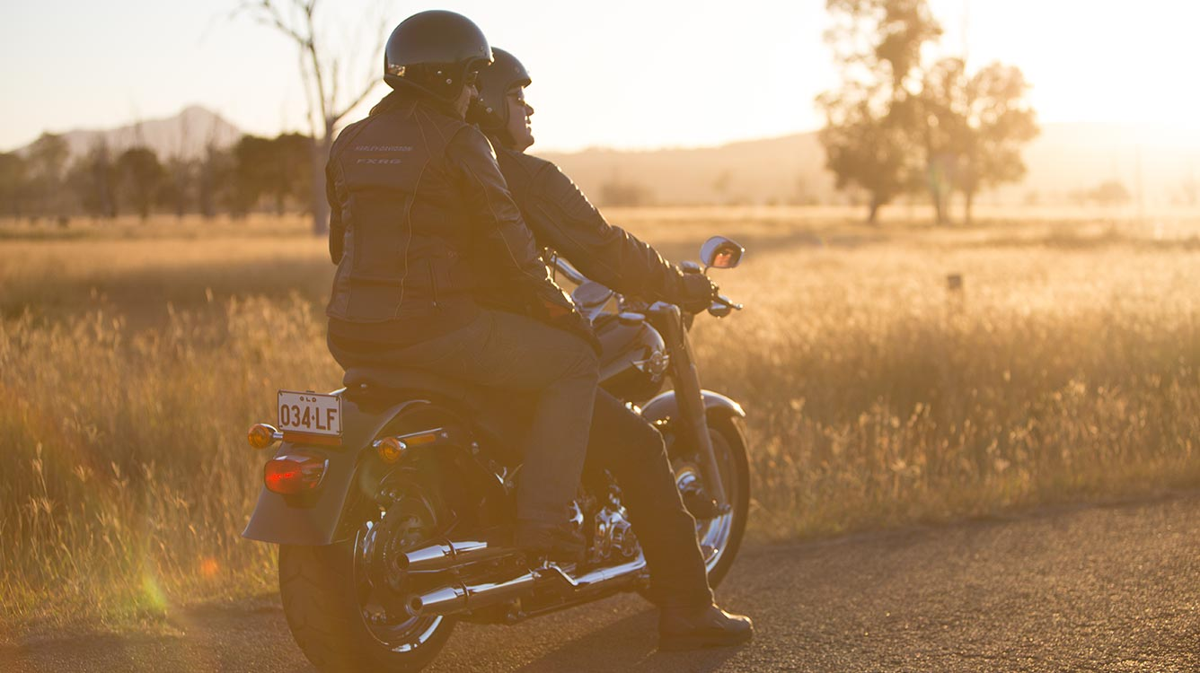 A man and a women sitting on a cruiser motorcycles looking at the sunset
