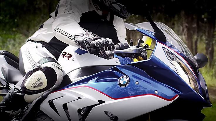 Close up shot of a rider wearing full white and black leather riding gear on a BMW S1000RR motorcycle