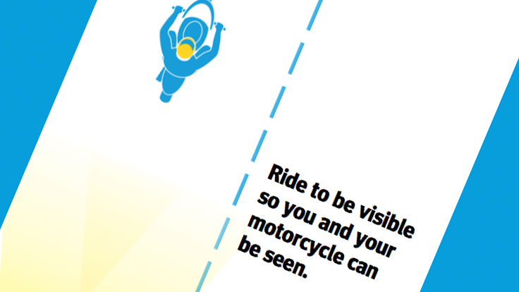 Top down view of cartoon motorcycle rider on one side of the dotted line with text on the other side saying: Ride to be visible so you and your motorcycle can be seen.