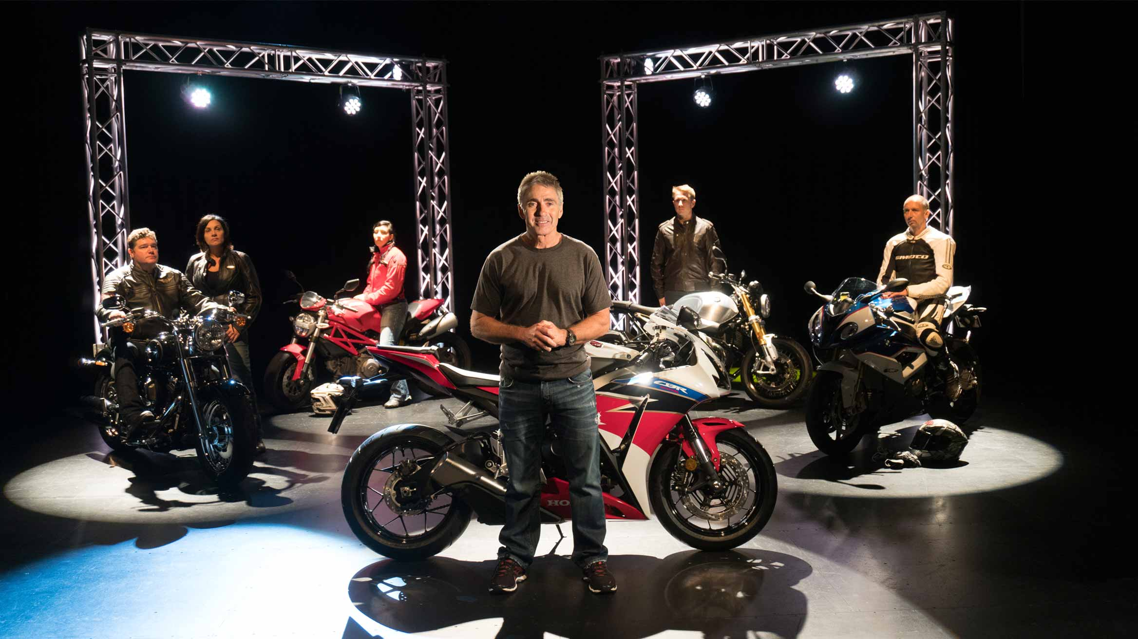 Mick Doohan standing infront of a motorcycle in a studio filled with lights and other various types of bikers featured behind him with their corresponding motorcycles