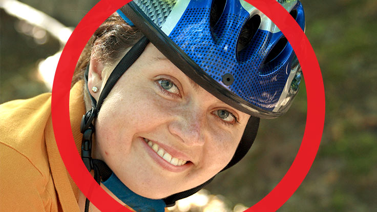 Portrait of lady with bicycle helmet on smiling at camera with thick red circle framing her face
