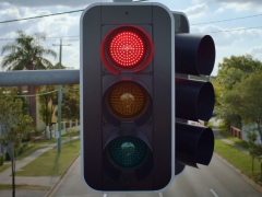 View of red light and young male clutching at the steering wheel of the car impatiently