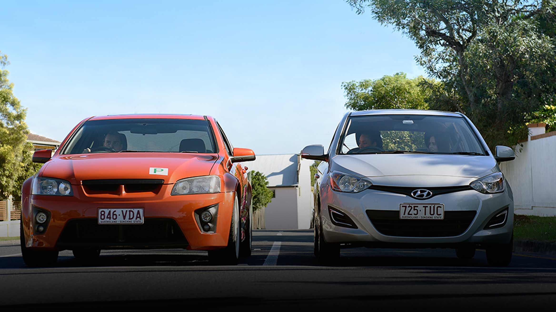 An orange car with P plates visible,  sitting next to a silver car with it's inhabitants looking at the orange car.