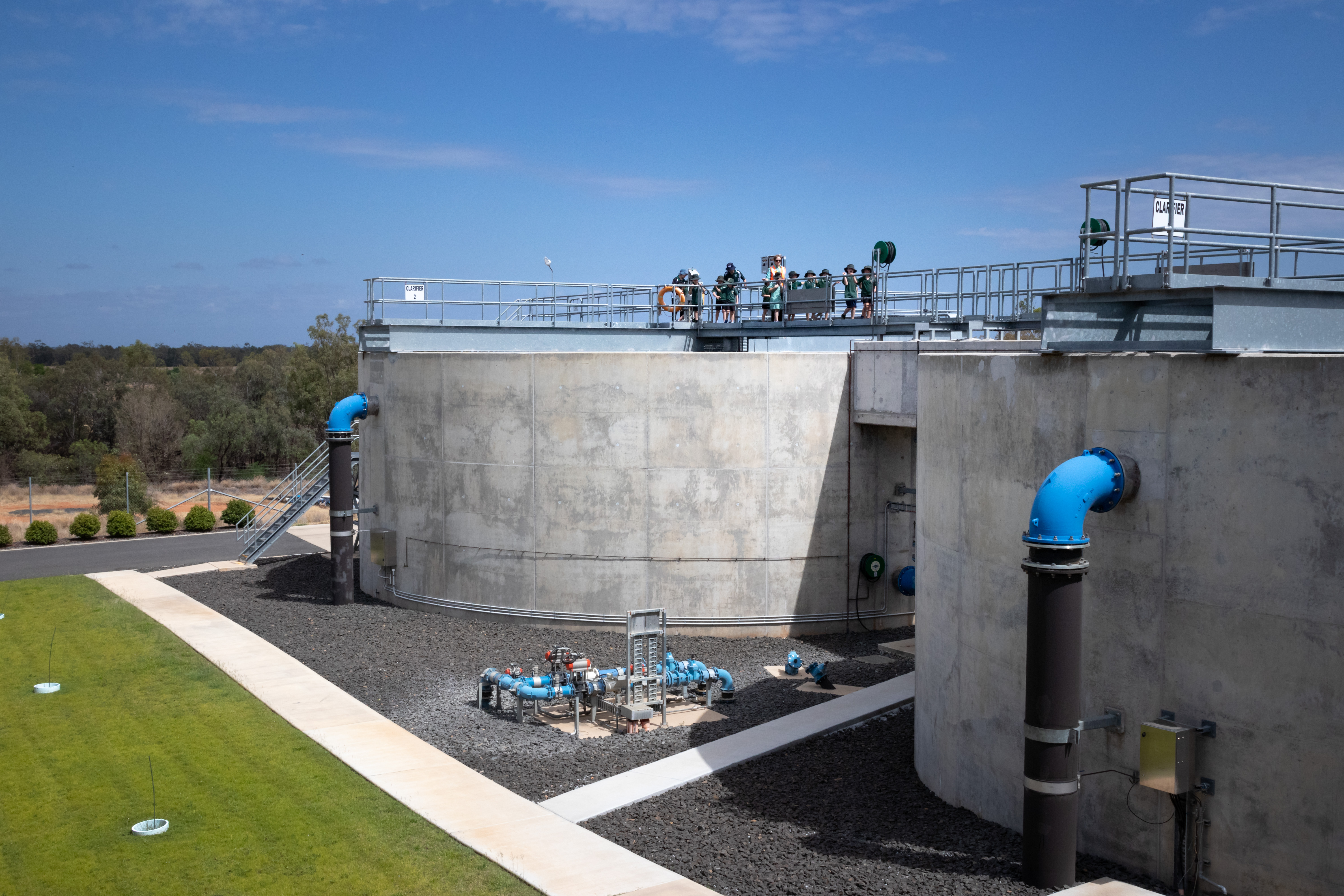 Water treatment plan - large water tanks near green lawn and with blue skies