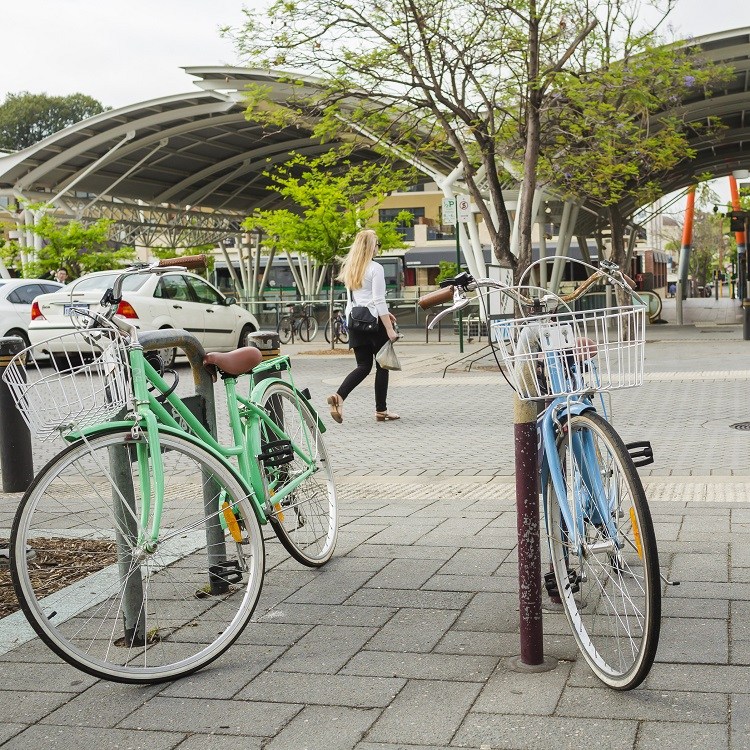 Image of bicycles and cars parked at train station with pedestrian in foreground