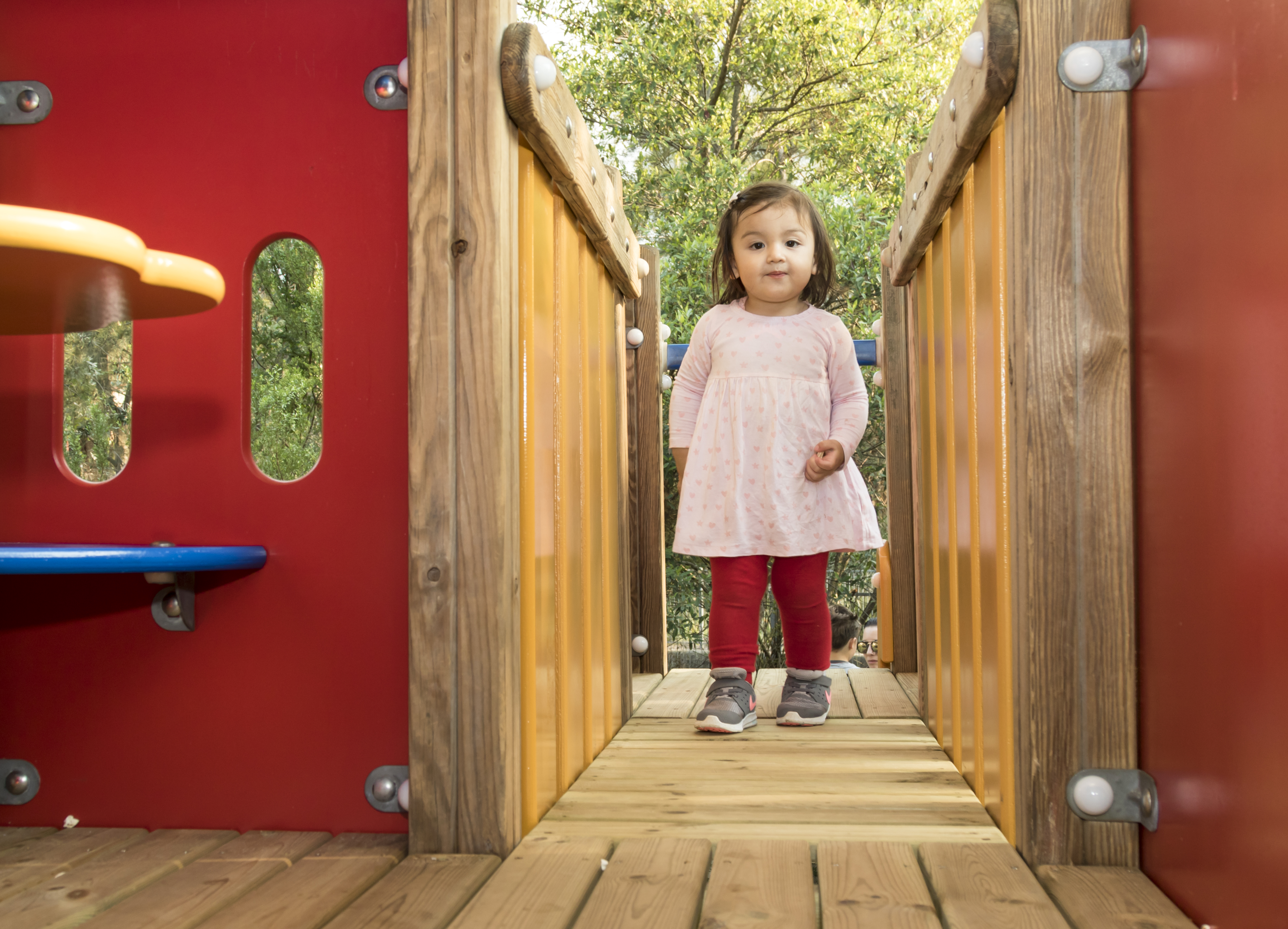 A young girl is walking across an imaginative play bridge. She is smiling.