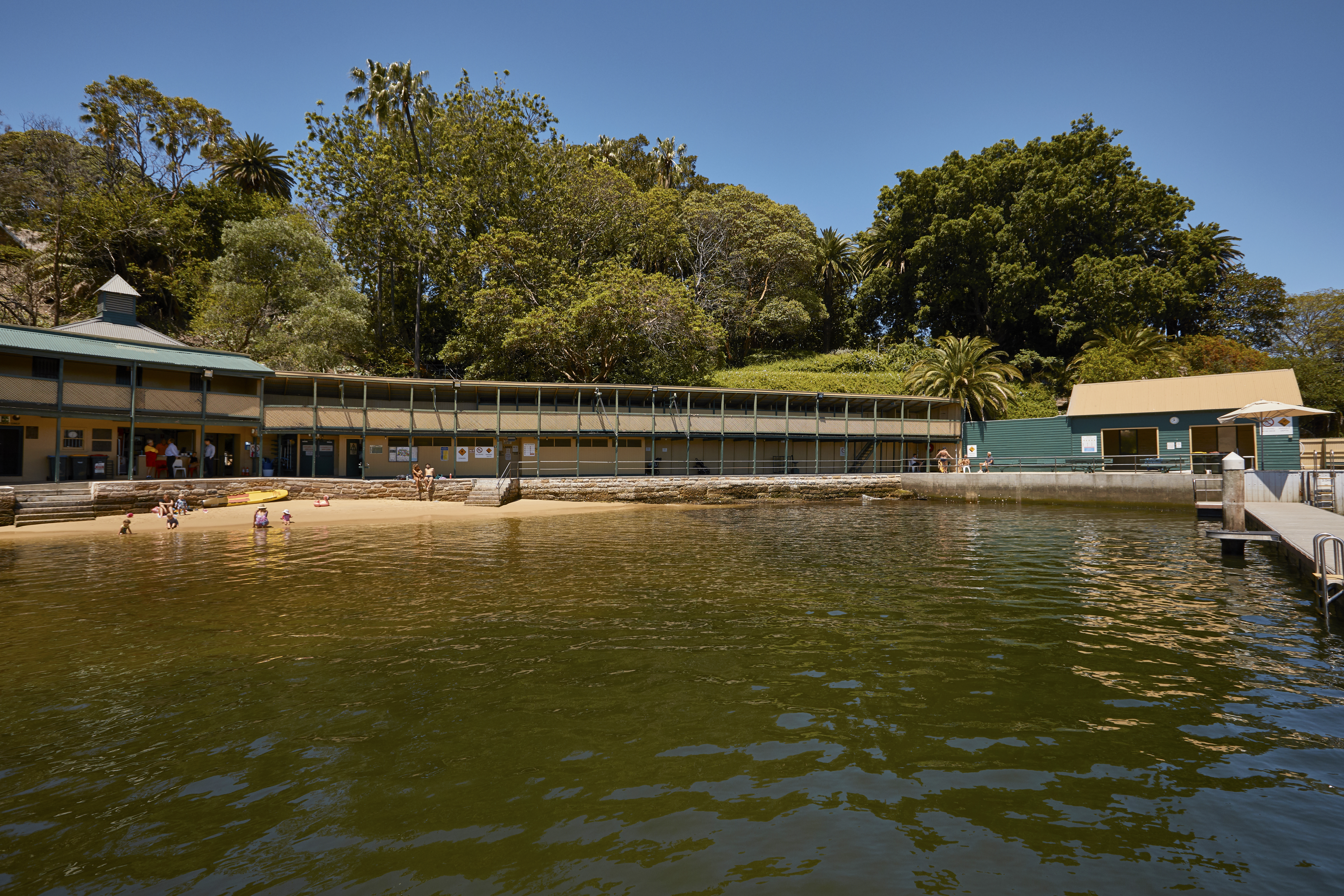 Looking across Dawn Fraser Baths with families padding at the water's edge on a sunny day.
