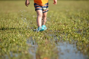 Child feet splashing mud