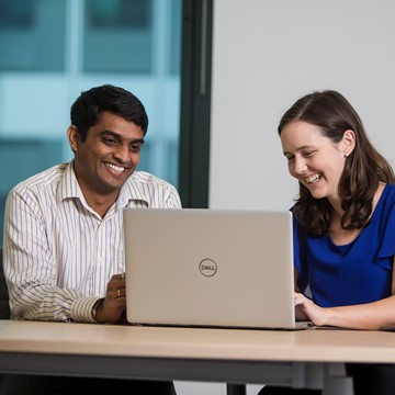 2 people looking at laptop.