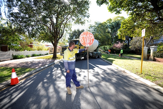 An image of a City employee with a stop sign. This is the link for the roads and traffic page.