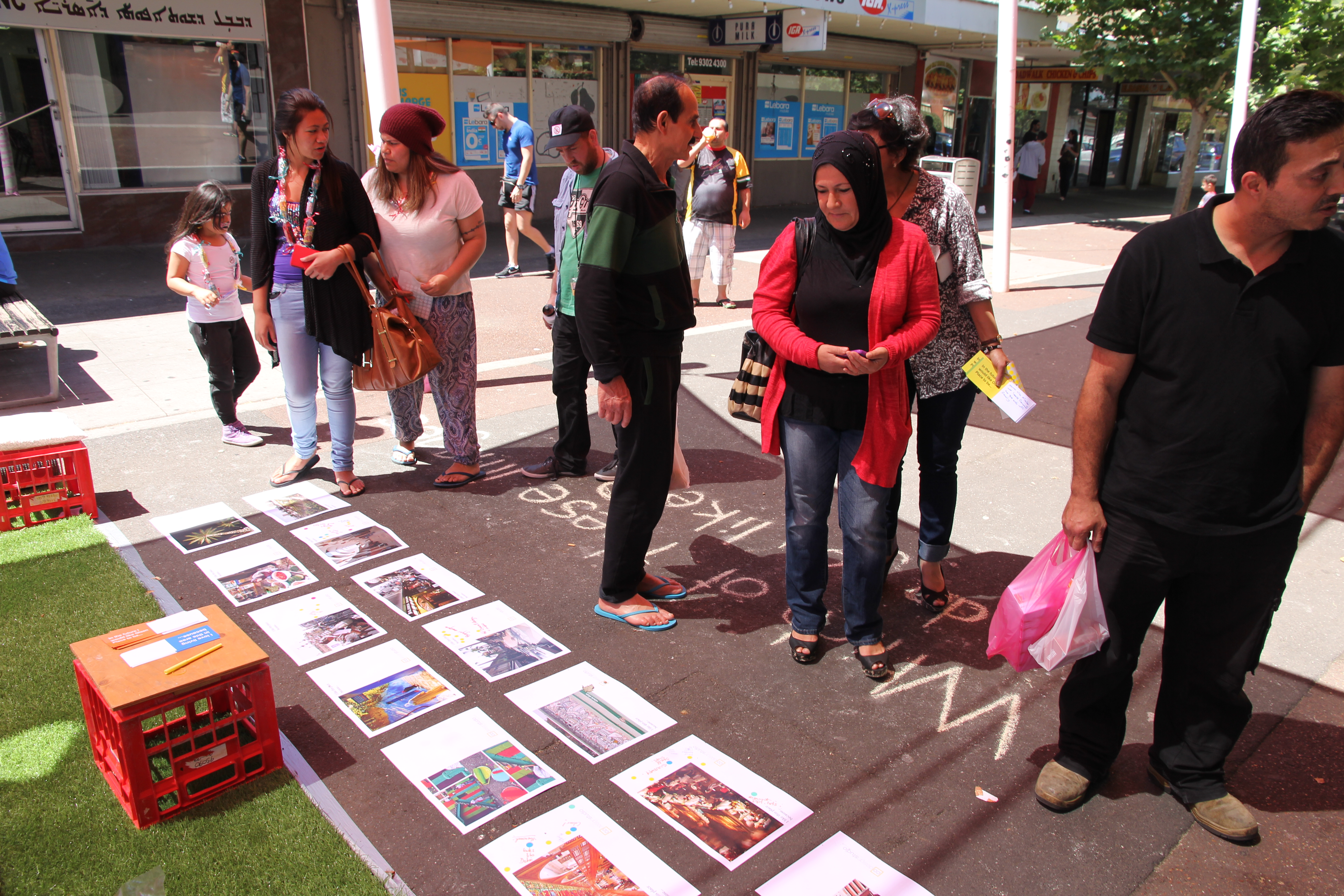 Six people looking at pictures on the ground showing different images