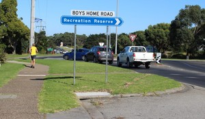Pedestrian and cars on boys home road roundabout