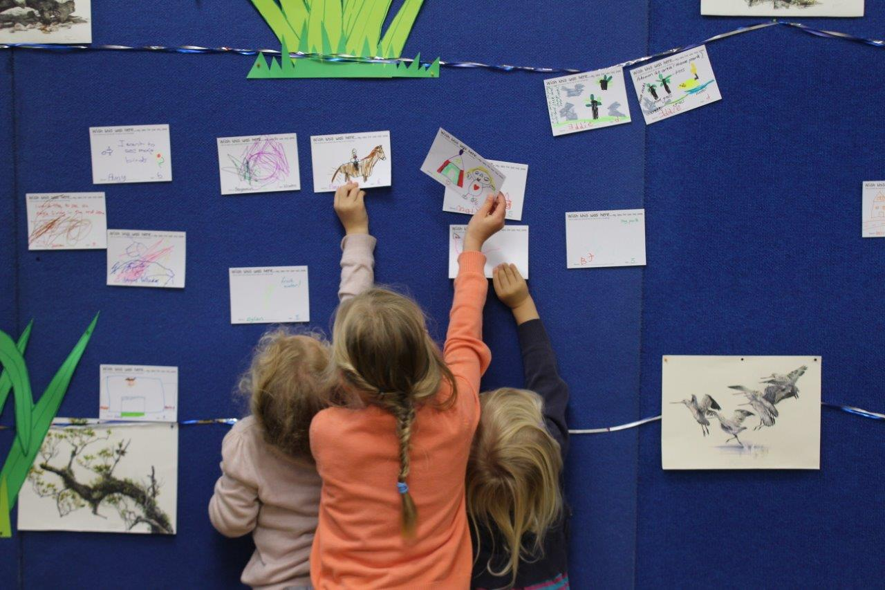 Photograph of children pinning their ideas for the Ōtākaro Avon River Corridor Regeneration Area onto a community noticeboard.