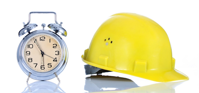 alarm clock and helmet on white background