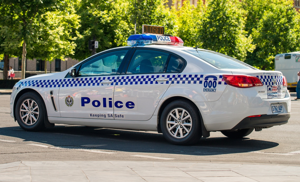 Adelaide, Australia - November 14, 2015: South Australian police car closed the street in  Adelaide's CBD with the policeman patrolling on the background (Adelaide, Australia - November 14, 2015: South Australian police car closed the street in  Adela