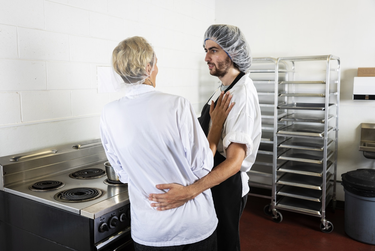 A male food service worker improperly touching a female colleague in a commercial kitchen.  He has his arm around her waist as she cooks at a stove. A concept on sexual harassment in the food service and restaurant industry.