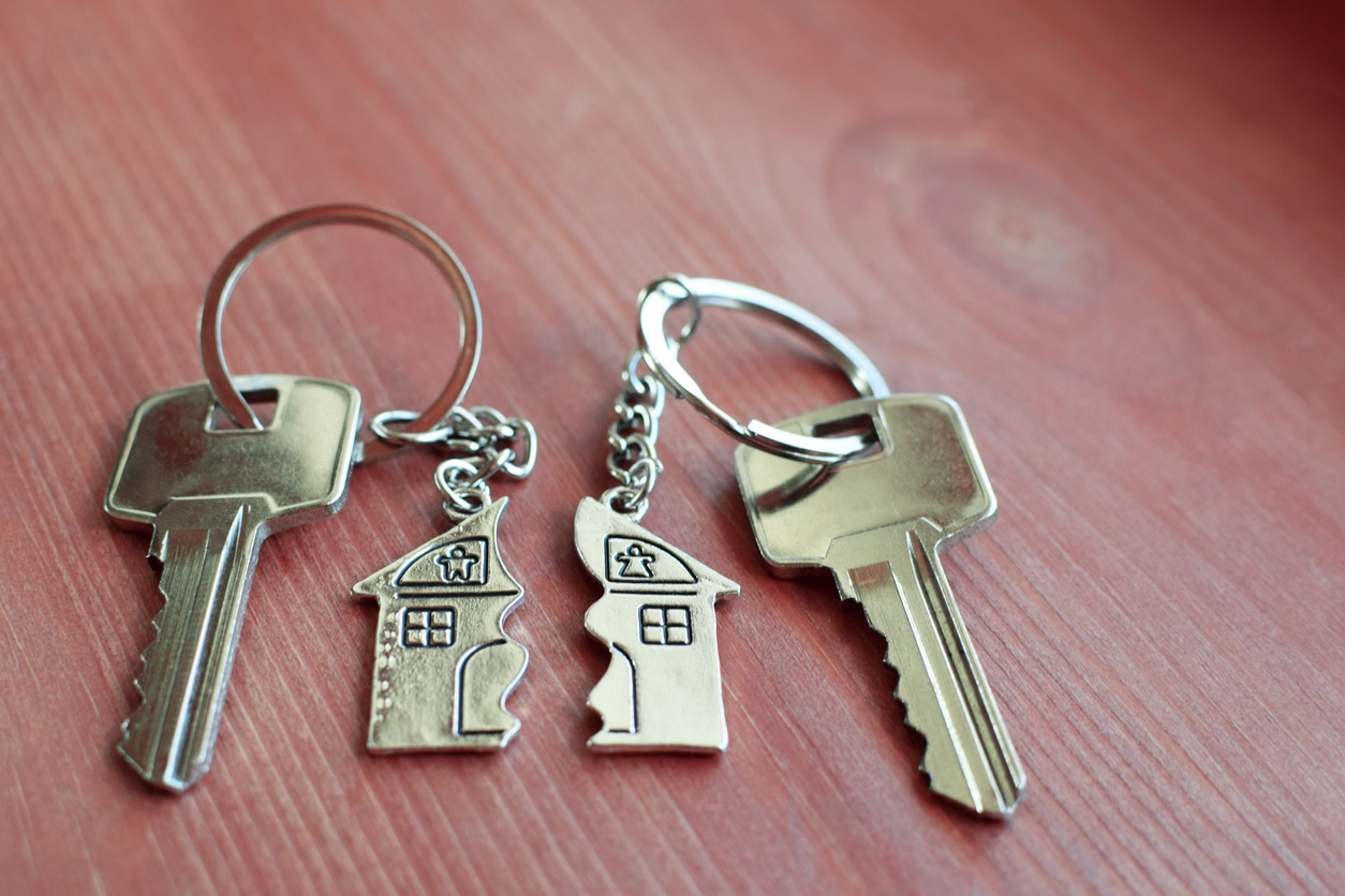 Two keys with splitted or broken key rings with pendant in shape of house divided in two parts on wooden background with copy space. Dividing house when divorce, division of property, real estate heritage.
