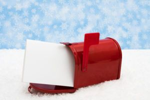 Red mailbox with the flag up sitting on snow with a snowflake background, mailbox