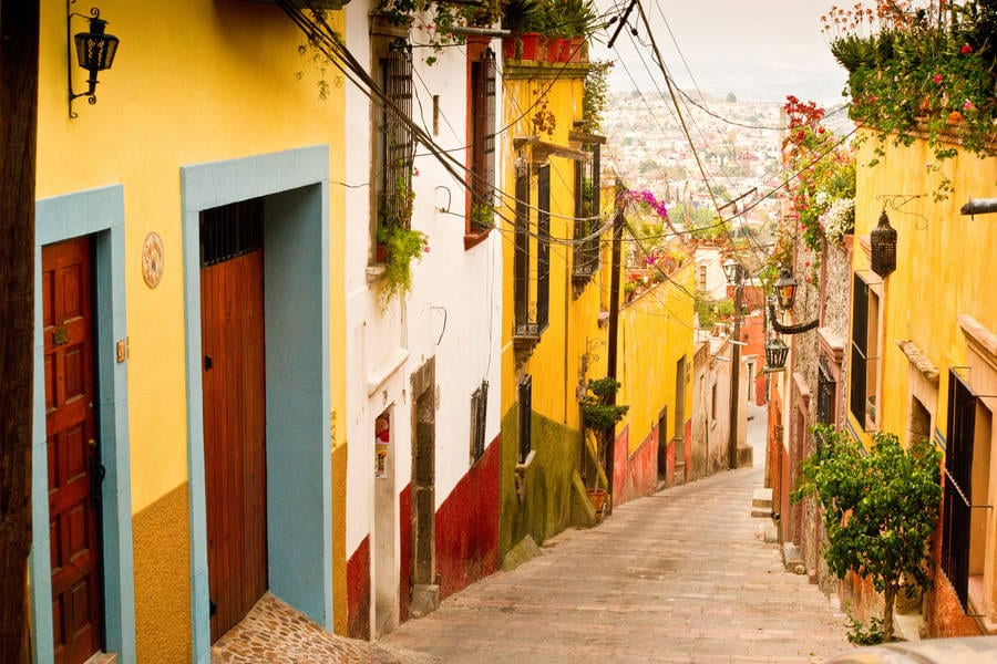 Photo looking down a colourful street int he Cayman Islands: Yellow walls and blue door frame