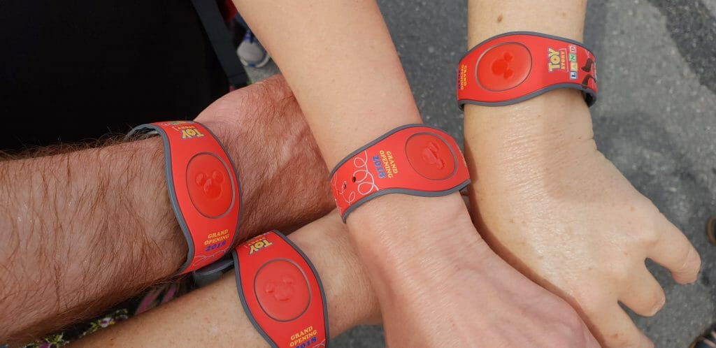 Four hands wearing Disney's Toy Story wristbands
