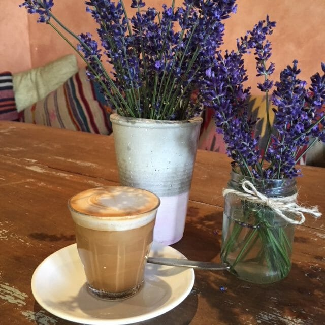 Latte in a clear glass on table with two pots of lavendar