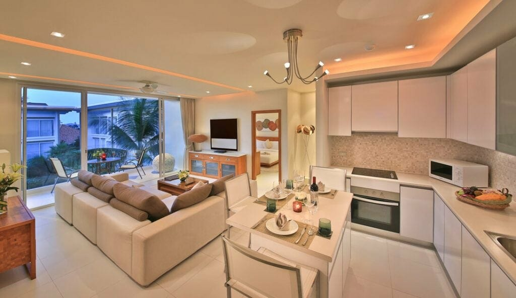 Photo of lounge room with kitchen in view