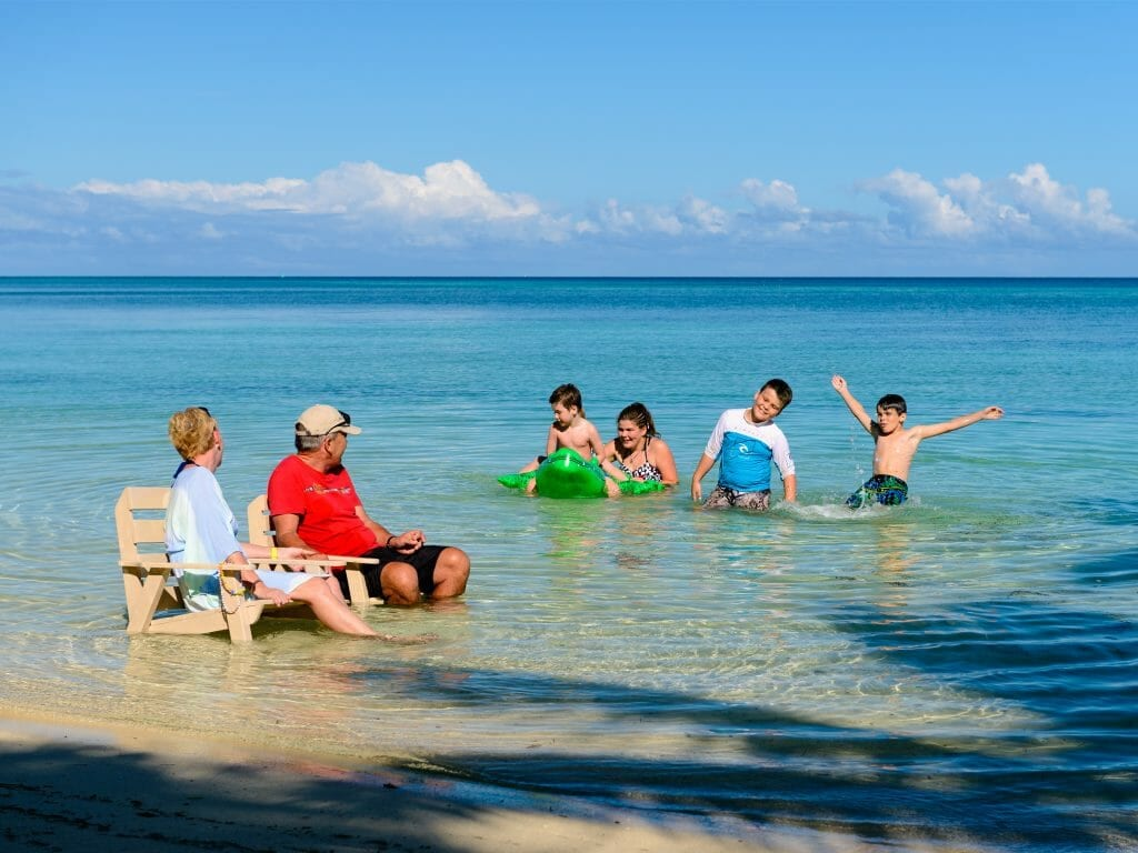 Grandparents and grandkids play in shallows of Fijian beach