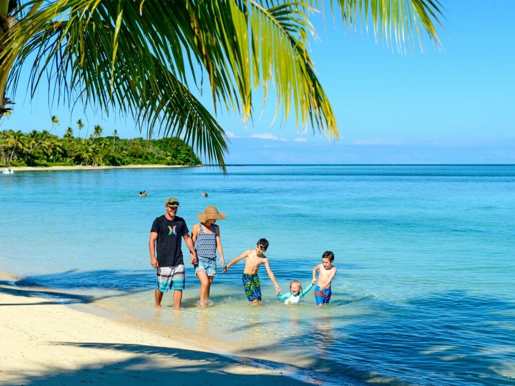 Family of five walk along tropical beach in Fiji