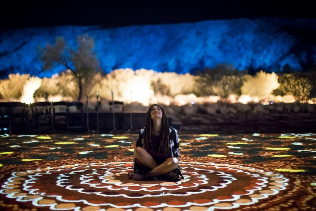 Girl sits on large-scale indigenous artwork at Parrtjima in Alice Springs