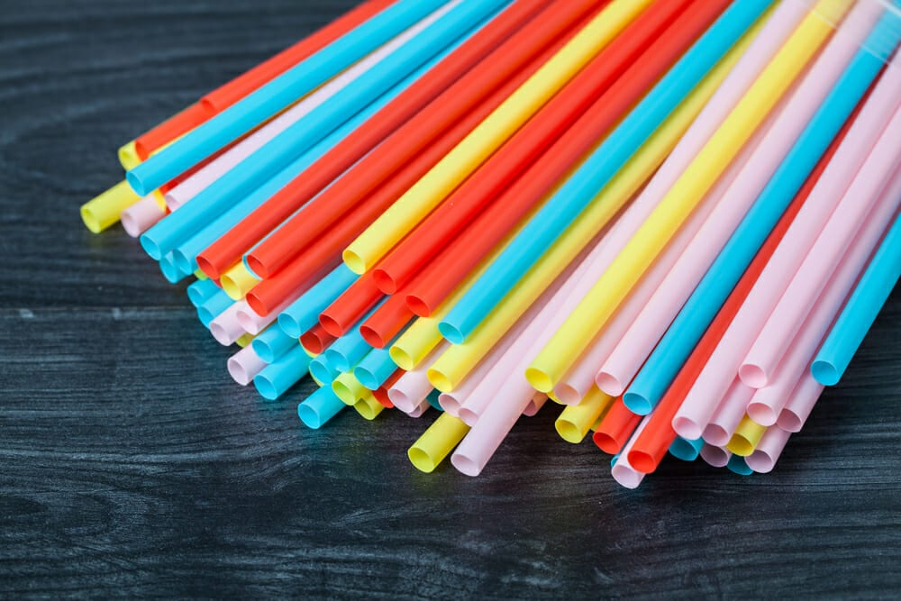 Packet of colourful plastic straws on table