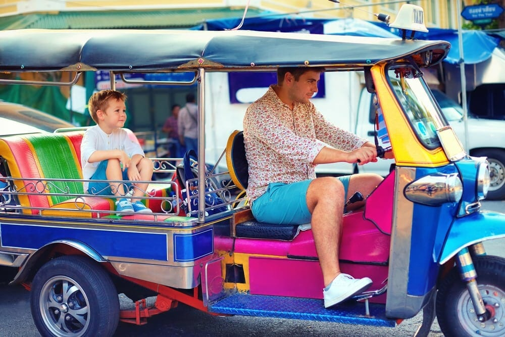 Dad drives colourful tuk tuk with child in back seat in Thailand