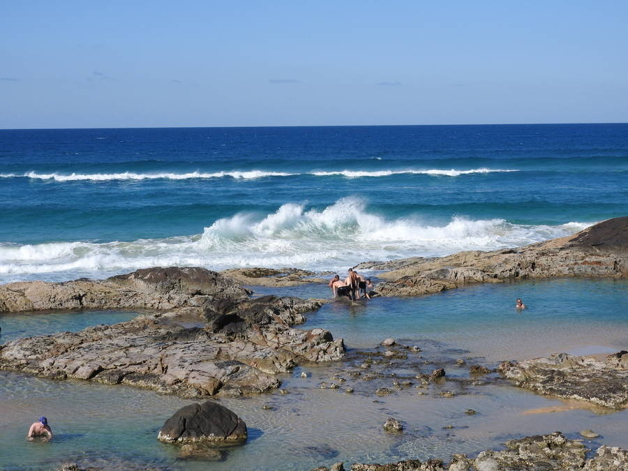 Kids swim in rock pools as waves crash