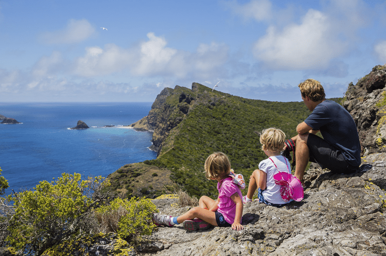 Two kids and father sit on edge of cliff overlooking water Australian islands