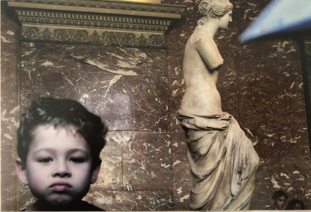 Young boy smirks in front of Venus di Milo in the Lourve