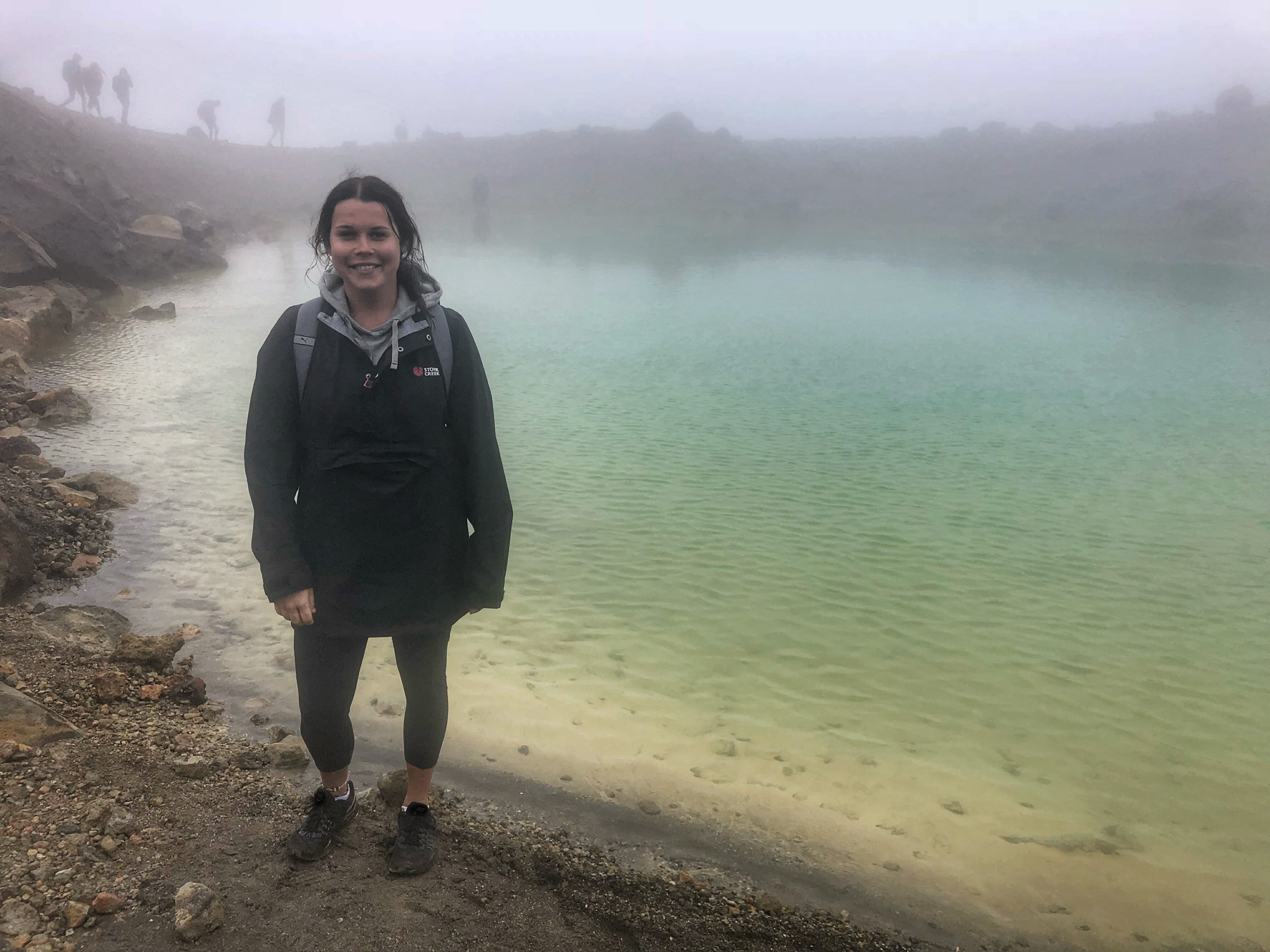 Girl standing in front of lake in wet weather