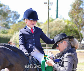 Ella Stringer holds judge Wedy Pollard's hat on whilst she's sashed Reserve Champion Junior Rider.... it was a little windy today!