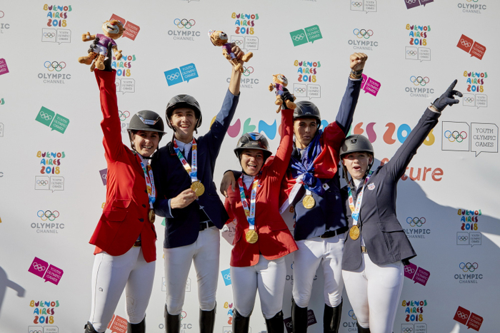 Everybody throw your hands up! Team North America celebrate their historic victory as they clinched the Team Gold medal in a nail biting jump off to top the podium at the Youth Olympic Games Buenos Aires 2018. L to R: Nicole Meyer Robredo, Pedro Espinosa, Marissa del Pilar Thompson, Mateo Philippe Coles, Mattie Hatcher Team USA, (FEI / Liz Gregg)