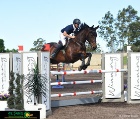 Leon Carroll and Delisch clear the final fence of the Open 1.30m A2 class in the main arena of the Sydney Summer Show Jumping Classic.