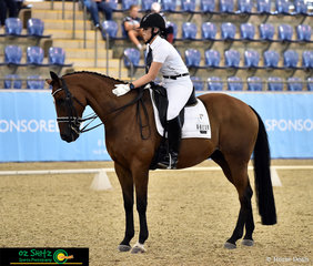 Hyperion recieves a pat from Cheraz Barker on completion of their Advanced dressage test in the indoor arena of the Sydney International Equestrian Centre.