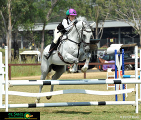 Eyes locked on the next jump, Grace Mackenzie and Belcam Japan Conac soar around the 90cm Secondary class at the NSW Interschool Championships held at SIEC in Sydney.