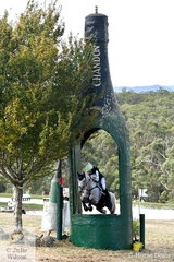 Lily Wickenden and 'Furst Sensation' are pictured jumping through the iconic Wandin Domaine Chandon Champagne bottle during the International Animal Health CCI3*.