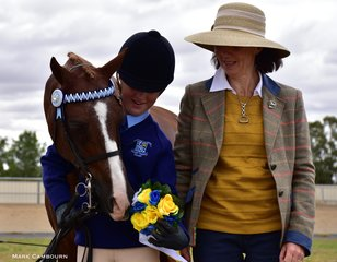 The Smart Family's Whitewood Just the Bees Knees inspects the floral rosette Judge Julie Vandyke awarded to his handler Brooke Kelly for Champion Interschools Handler.