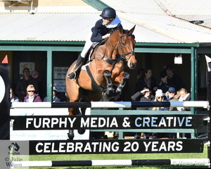 Tara Rogers and the jumping bred, 'Denison Park Smooth' make a lovely jump over the naming sponsor's fence on their way to seventh place in the  Horseware Australia CCI3*-L.